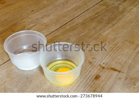 Raw egg and sugar in cup on the wood table - stock photo