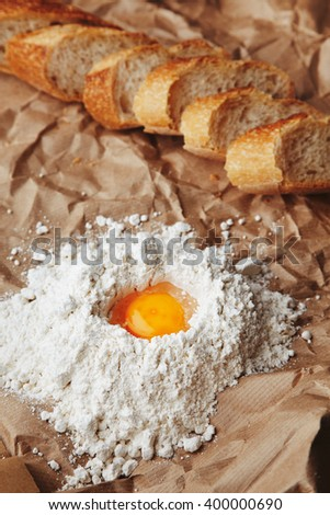Raw egg broken in white flour on craft paper near sliced french crunched freshly baked baguette bread. Yolk in center on flour pyramide - stock photo