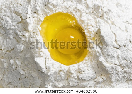 Raw egg in flour on the kitchen table closeup