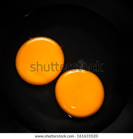 Raw egg yolk detail on black background - stock photo