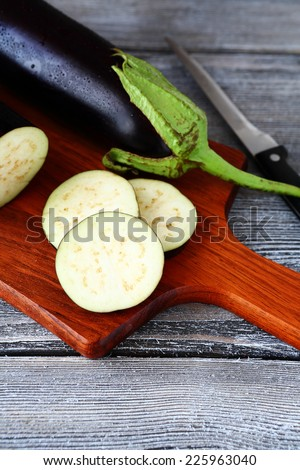 Raw eggplant and cutting boards, wooden background - stock photo