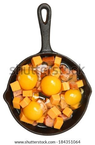 Raw Eggs, Cheese and Sausage in Cast Iron Skillet Isolated Over White. - stock photo