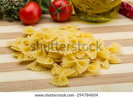 Raw farfalle Italian pasta on the wood board - stock photo