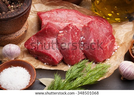 Raw fillet beef steak and spices on stone board - stock photo