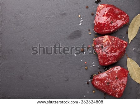 Raw fillet beef steak and spices on stone board. Top view with copy space - stock photo