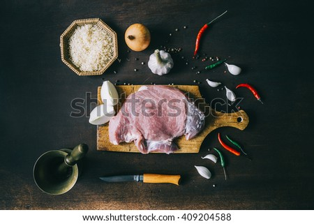 Raw fillet pork steak and spices on wooden table. Top view. Rice, onion, garlic, chili peppers,knife, mortar and pestle. - stock photo