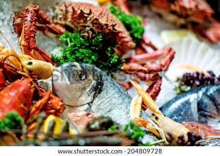 Raw Fish, crab and other seafood on ice - stock photo