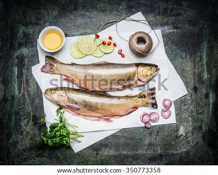 Raw fish on white paper with ingredients for cooking, top view. Two whole Char fish. Healthy food or diet nutrition concept. - stock photo