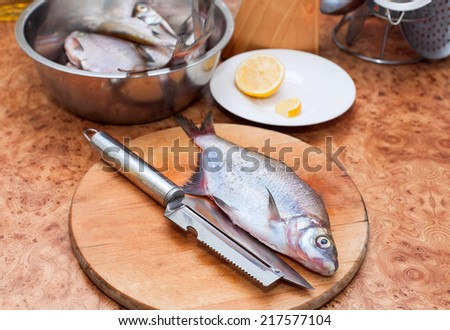raw fish on wooden cutting board with knife in the kitchen, gorizontal - stock photo