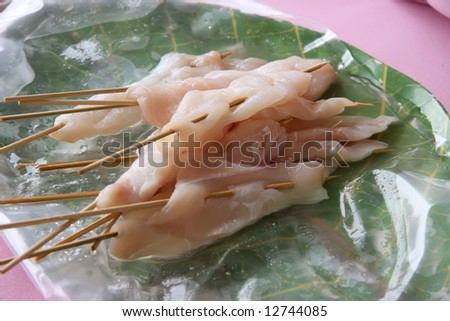 Raw fish on wooden skeweres prepared for grilling