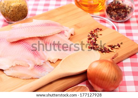Raw fish tlapia on cutting board with spices, herbs and seasonings, selective focus - stock photo