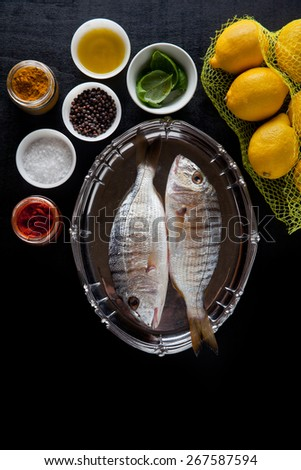 raw fish with cooking ingredients - stock photo