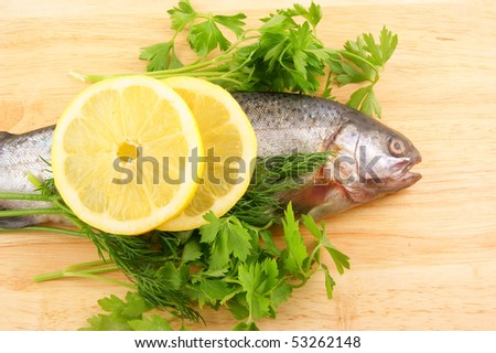 Raw fish with lemon and parsley on wooden background