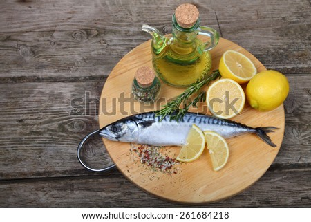 Raw fish with lemon and rosemary on a wooden board - stock photo