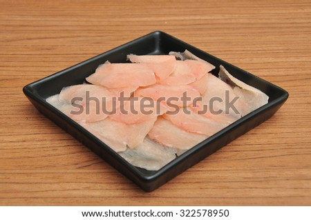 Raw fish with sesame on black plate - stock photo