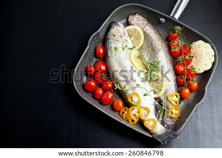 raw fish with vegetables in pan - stock photo