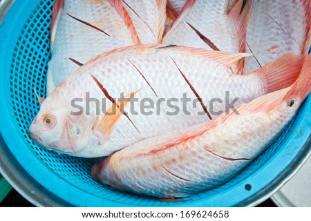 Raw fishes in basket for cooking - stock photo