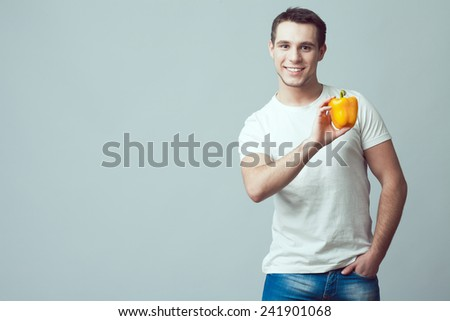 Raw food concept. Portrait of smiling good looking boy in casual clothing holding yellow pepper over gray background. Healthy skin, bristle face, hand in pocket. Close up. Copy-space. Studio shot - stock photo