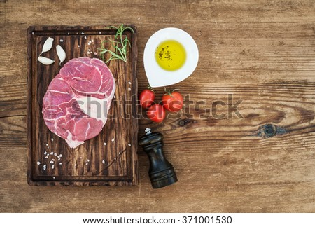 Raw fresh beef meat cross cut for ossobuco cut with garlic cloves, cherry tomatoes, rosemary, pepper, oil and salt on serving board over rustic wooden background, top view, copy space - stock photo