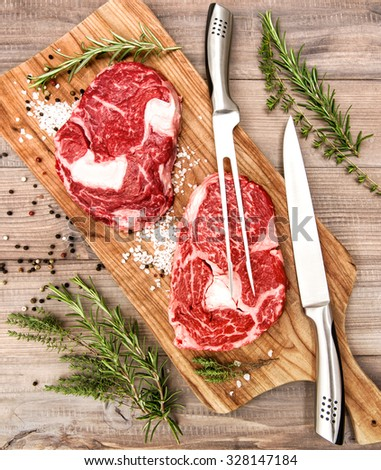 Raw fresh beef meat Rib Eye Steak with herbs and spices on wooden desk. Fork and knife for food preparation.  - stock photo