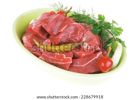 raw fresh beef meat slices in a ceramic dish with onion and red peppers isolated over white background - stock photo
