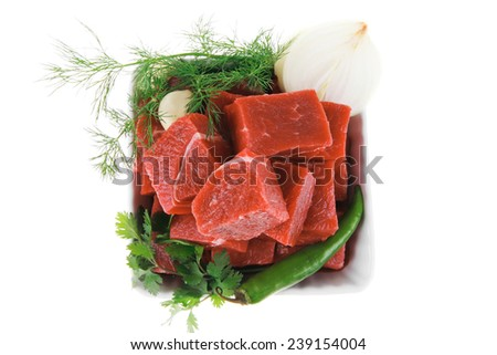 raw fresh beef meat slices in a white bowls with dill and green hot peppers isolated over white backkground - stock photo