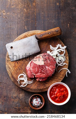 Raw fresh cross cut veal shank and Ingredients for making Osso Buco on wooden cutting board on dark wooden background - stock photo