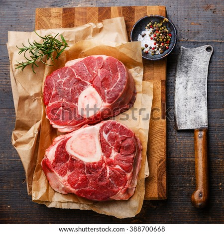 Raw fresh cross cut veal shank and seasonings for making Osso Buco on wooden cutting board with meat cleaver - stock photo