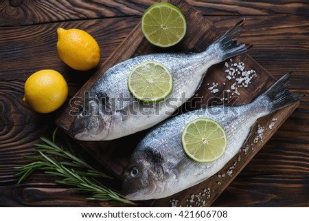Raw fresh dorado fish in a rustic wooden setting, high angle view - stock photo