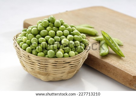 Raw fresh green peas in cane container along with chopping board - stock photo