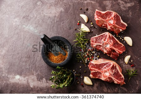 Raw fresh lamb loin chops with herbs and spices on stone slate plate - stock photo
