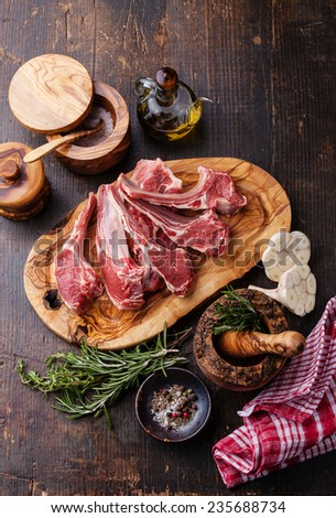 Raw fresh Lamb Meat ribs and seasonings on dark wooden background - stock photo