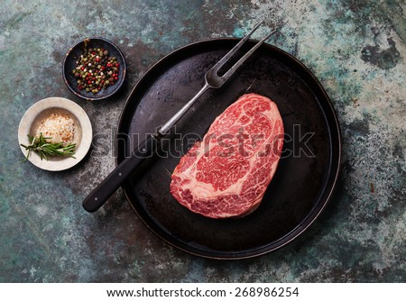Raw fresh marbled meat Black Angus Steak and seasonings on metal background - stock photo
