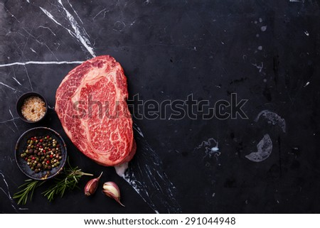 Raw fresh marbled meat Black Angus Steak Ribeye and seasonings on dark marble background  - stock photo