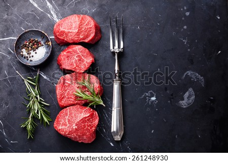 Raw fresh marbled meat Steak, seasonings and meat fork on dark marble background  - stock photo