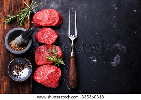 Raw fresh marbled meat Steaks with seasonings and meat fork on dark marble background - stock photo