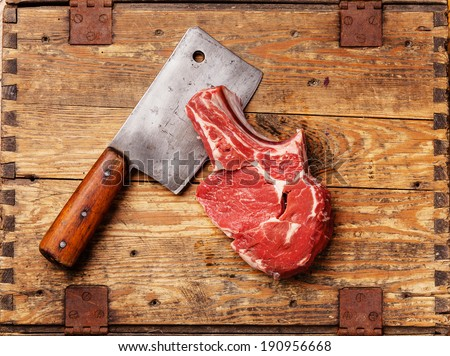 Raw fresh meat and meat cleaver on wooden background  - stock photo