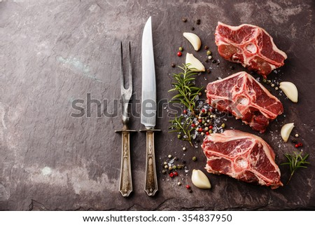 Raw fresh meat lamb mutton saddle with herbs and spices on stone slate plate - stock photo