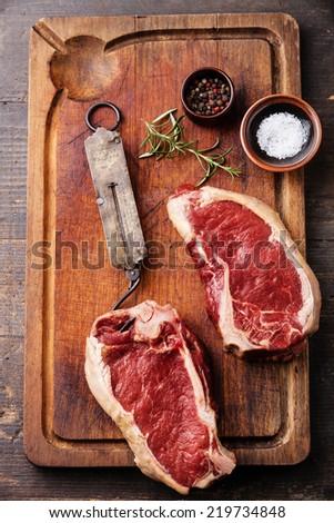 Raw fresh meat Ribeye Steak, seasoning and vintage steelyard on dark background - stock photo