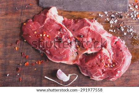 Raw fresh meat Ribeye Steak, with seasoning and meat axe on vintage wooden board - stock photo