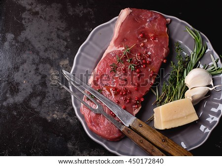 Raw fresh meat Striploin steak and seasoning on a grey vintage plate over dark metal background, top view - stock photo