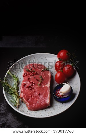 Raw fresh meat Striploin steak and seasoning on a spotted plate over dark metal background, top view