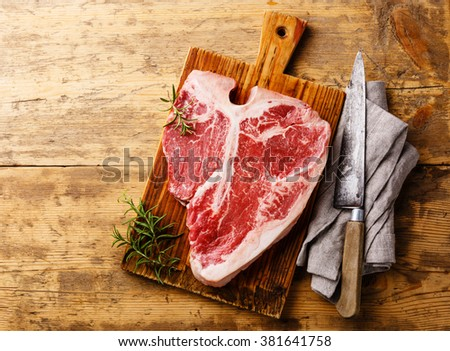 Raw fresh meat T-bone steak and kitchen knife on wooden background - stock photo