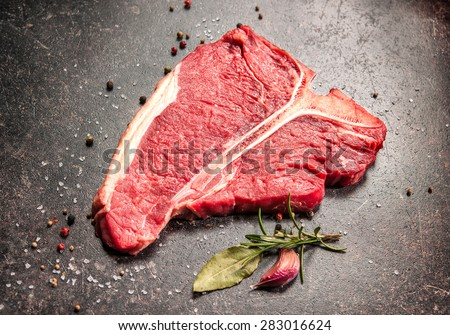 Raw fresh meat T-bone steak and seasoning on dark background - stock photo