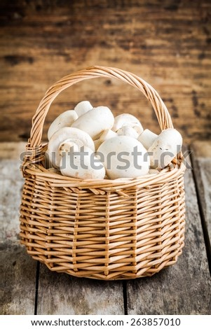 raw fresh mushrooms in  the basket on a rustic wooden table - stock photo