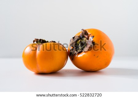 Raw fresh persimmons isolated on white background.