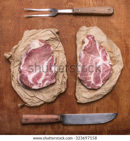 raw fresh pork steak with old knife  and meat fork  on rustic wooden background top view close up - stock photo