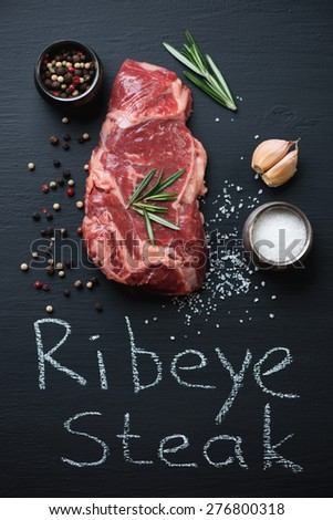 Raw fresh ribeye steak with salt, pepper, garlic and rosemary - stock photo