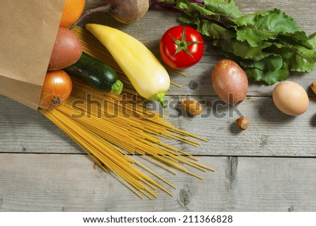 raw fruits and vegetables, pasta and eggs rolling from paper bag on weathered wooden table - stock photo