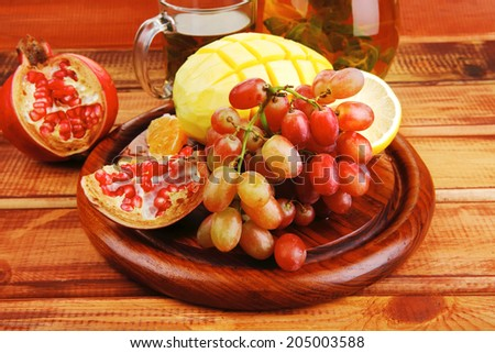 raw fruits served with tea on wood - stock photo